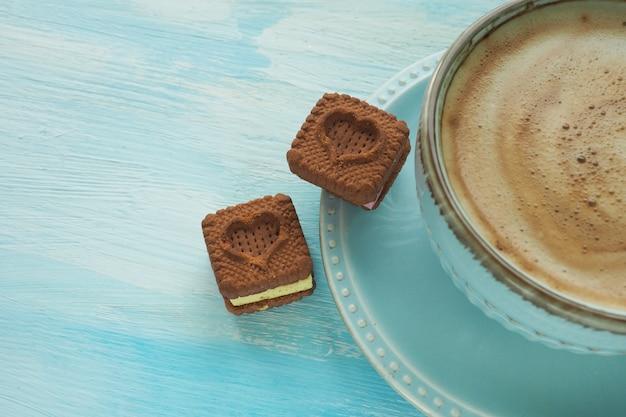 Zwei herzförmige kekse auf einer untertasse in der nähe einer tasse kaffee.