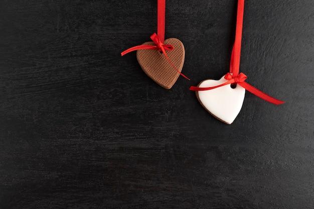 Zwei herzförmige lebkuchenplätzchen hängen vom roten band, schwarzer hintergrund. muttertag. frauentag. valentinstag.
