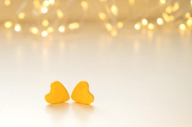 Zwei herzförmige pillen auf verschwommenen bokeh-lichtern