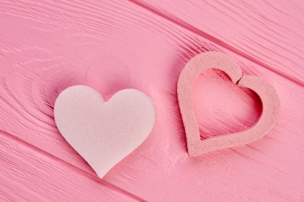 Zwei herzformen auf rosa holz. herzbimssteine auf buntem hölzernem hintergrund. valentinstag design.