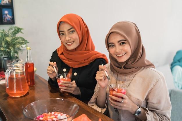 Zwei hijab frau, die cocktailgetränk trägt