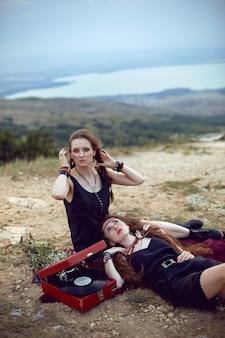 Zwei hippiefrauen liegen auf einem feld auf einem berg mit einem alten grammophon auf einer schallplatte