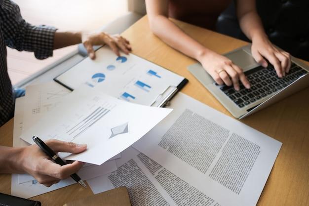 Zwei hochschulstudenten, die zusammen mit laptop- und prüfungsdokumenten in einem café / in einer bibliothek arbeiten
