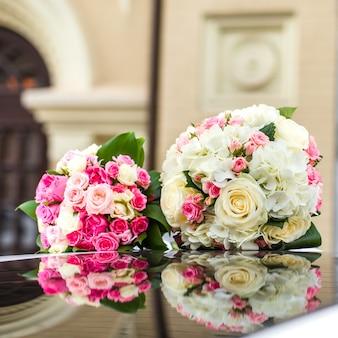 Zwei hochzeitsblumenstrauß von rosen auf einer spiegeloberfläche