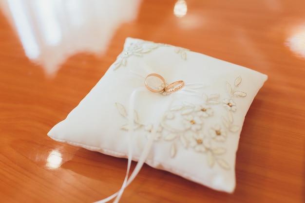 Zwei hochzeitsgoldringe, die auf silk spitzekissen für ringe liegen. hochzeitszubehör braut und bräutigam vor der zeremonie fotografierte auf einem weißen hintergrund. ringe am hochzeitstag.
