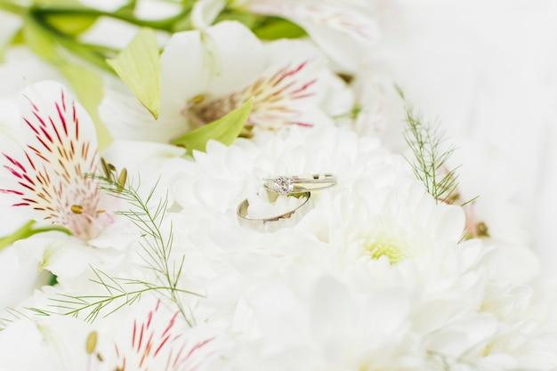 Zwei hochzeitsringe auf schönen blumen der chrysantheme und der peruanischen lilie
