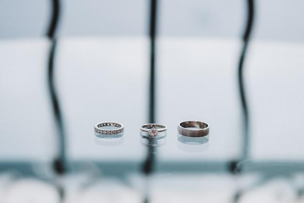 Zwei hochzeitsringe und ein verlobungsring getrennt auf einer glastabelle