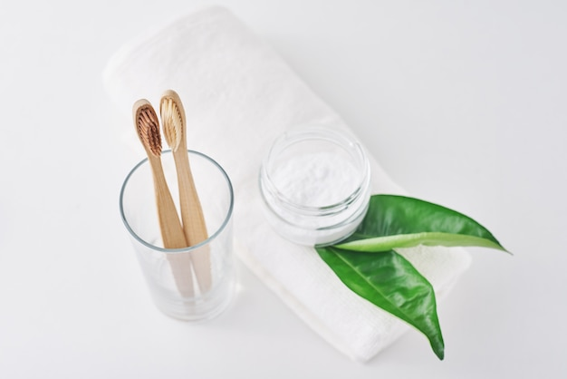 Zwei hölzerne bambus-eco freundliche zahnbürsten in einem glas, in einem backnatron und in einem tuch auf weißem hintergrund.