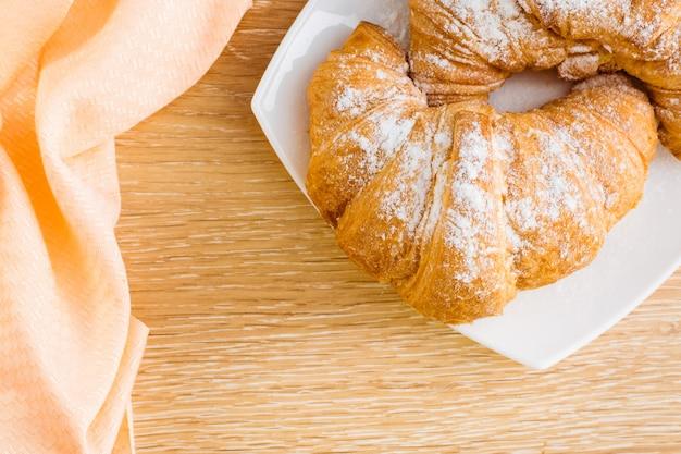 Zwei hörnchen im puderzucker auf einer weißen platte auf einem holztisch