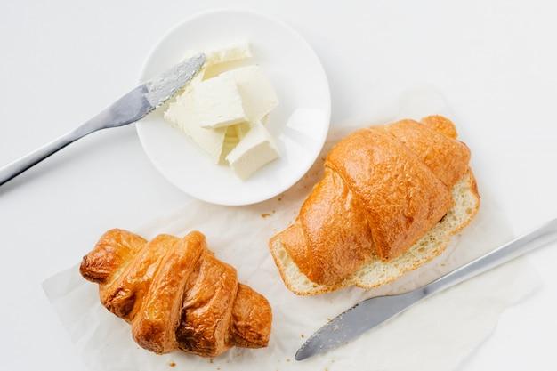 Zwei hörnchen und butter auf weißer tabelle, draufsicht.