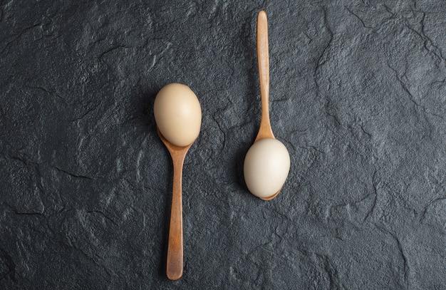 Zwei holzlöffel rohe eier auf schwarzem hintergrund