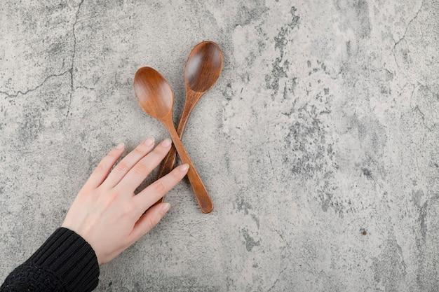Zwei holzlöffel und weibliche hand auf marmorhintergrund
