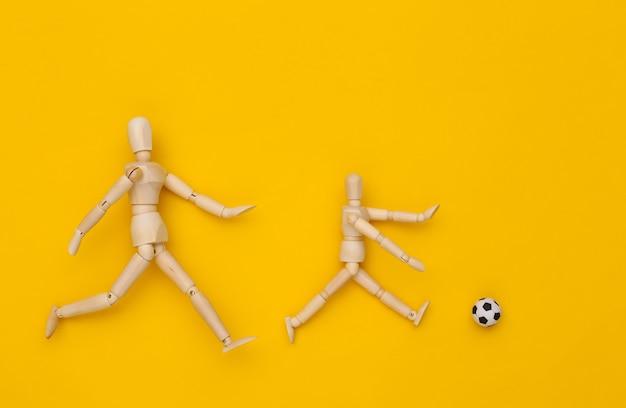 Zwei holzpuppen, die fußball mit einem ball auf gelbem hintergrund spielen
