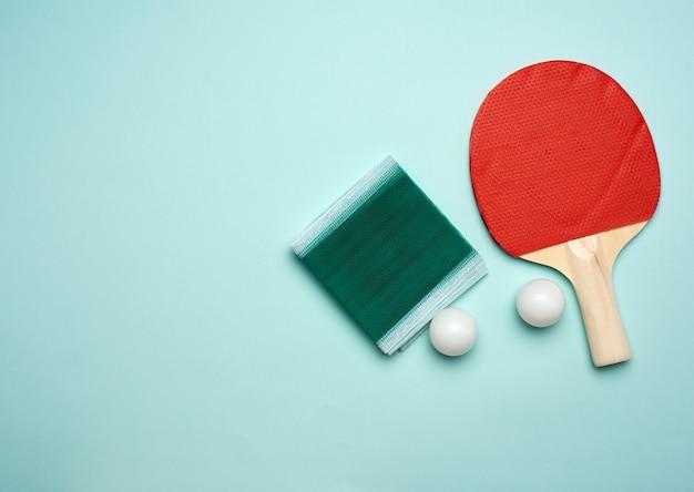 Zwei holzschläger und ein orangefarbener plastikball zum tischtennis