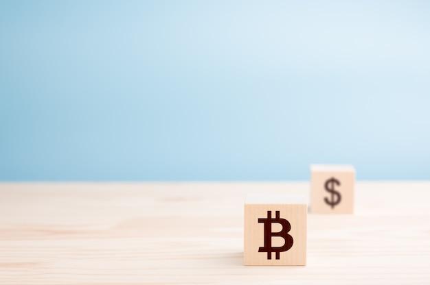 Zwei holzwürfel mit dollar- und bitcoin-symbolen auf blau