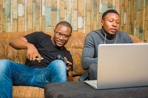 Zwei hübsche afrikaner sitzen auf der couch und spielen videospiele mit joystick, gamepad, pad