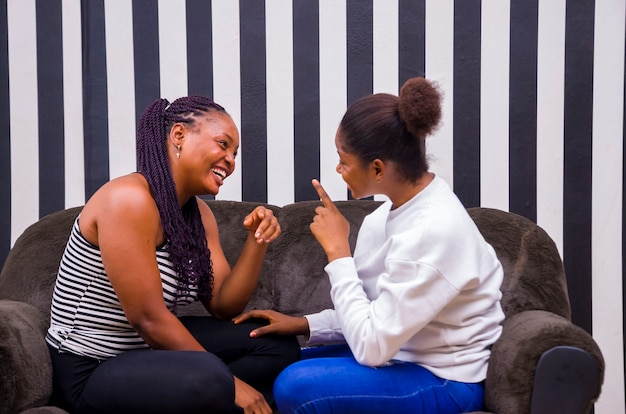 Zwei hübsche afrikanische damen sind überglücklich, während sie diskutieren