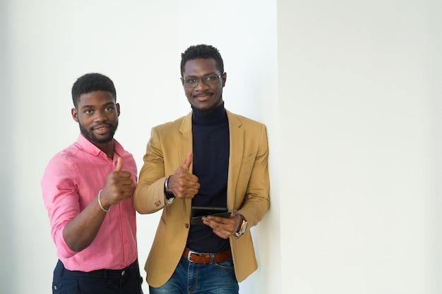 Zwei hübsche afrikanische männer im amt mit handgeste