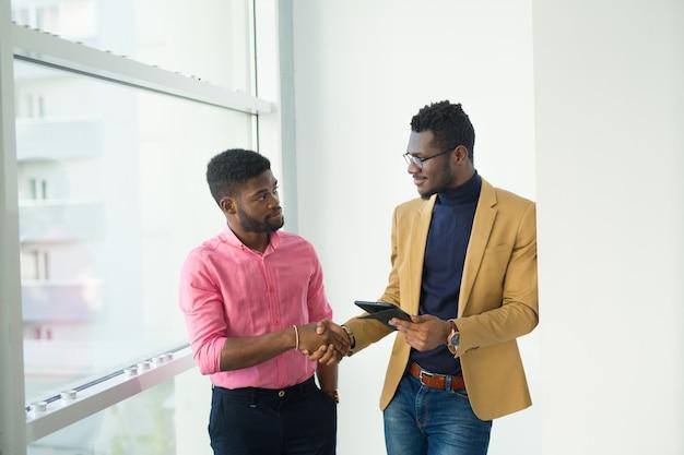 Zwei hübsche afrikanische männer im büro händeschütteln