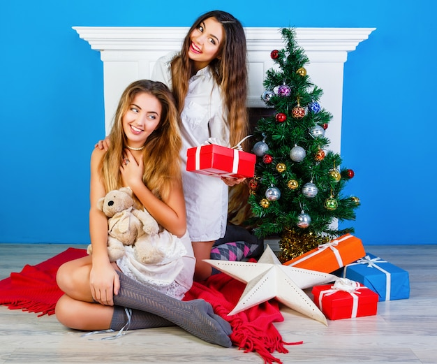 Zwei hübsche beste freundinnen, die weihnachtsgeschenke nahe kamin öffnen und neujahrsbaum schmücken. in den winterferien gemeinsam spaß haben.