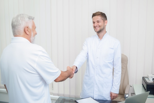 Zwei hübsche doktoren, die hände im hellen kabinett rütteln.