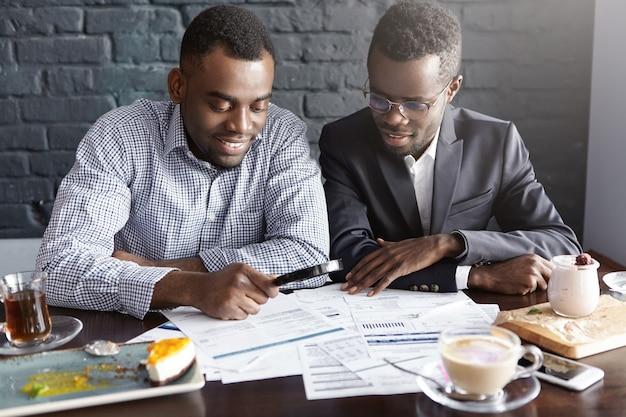 Zwei hübsche erfolgreiche afroamerikanische geschäftsleute, die lupe verwenden