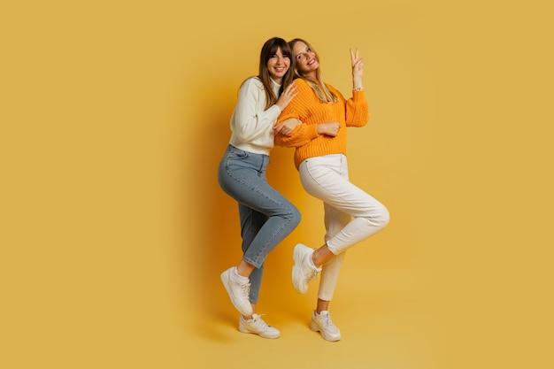 Zwei hübsche frauen, beste freunde in stilvoller herbstkleidung, die spaß auf gelb haben. volle länge.