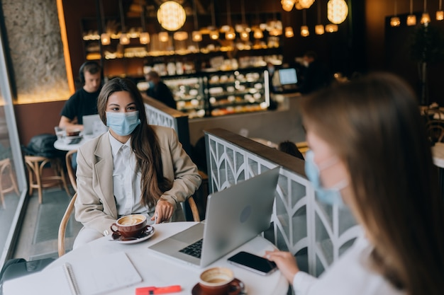 Zwei hübsche frauen, die medizinische gesichtsmaske tragen, die laptop verwendet, um zu arbeiten