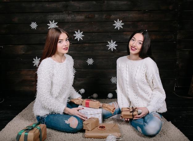 Zwei hübsche frauen, die mit geschenken für weihnachten aufwerfen