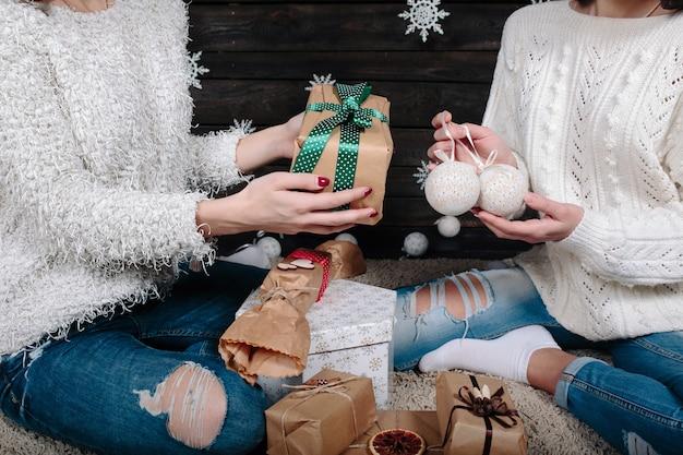 Zwei hübsche frauen, die mit geschenken für weihnachten, nahansicht aufwerfen