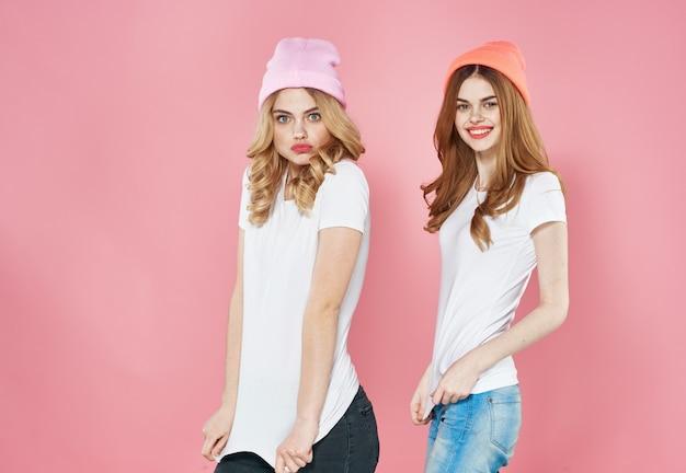 Zwei hübsche frauen, die modische kleiderstudios der rosa hüte tragen, beschnittenen blick des modells