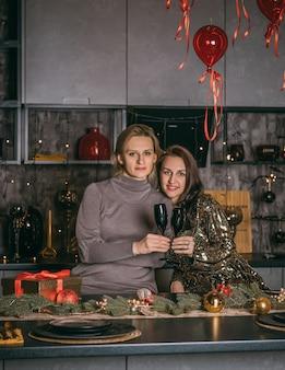 Zwei hübsche frauen feiern die weihnachtsferien auf dem festlichen haushintergrund.