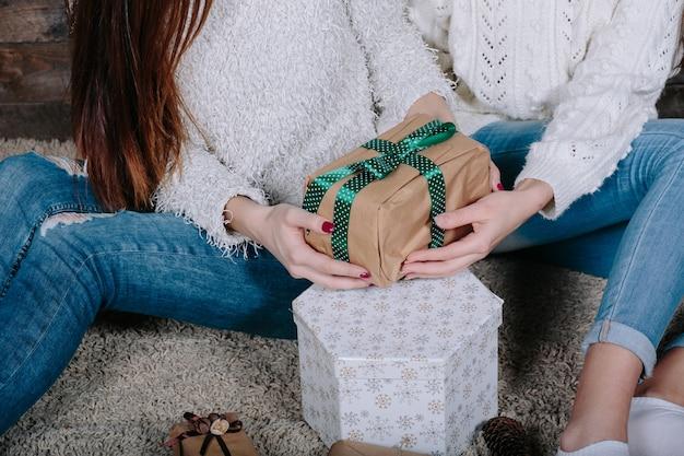 Zwei hübsche frauen mit geschenken für weihnachten, nahansicht