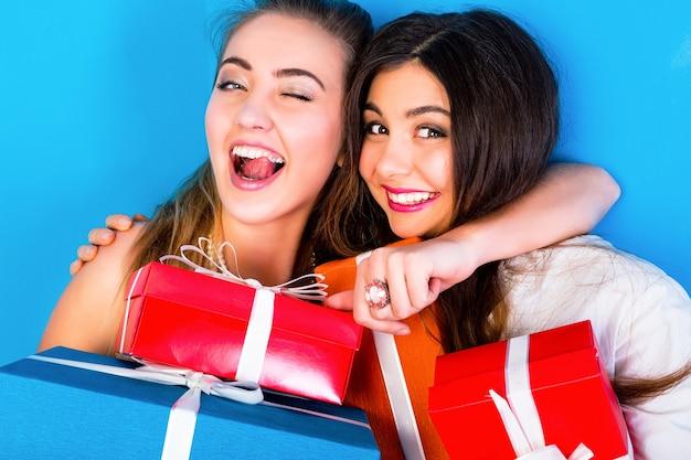 Zwei hübsche freundinnen, die helle feiertagsgeschenke halten