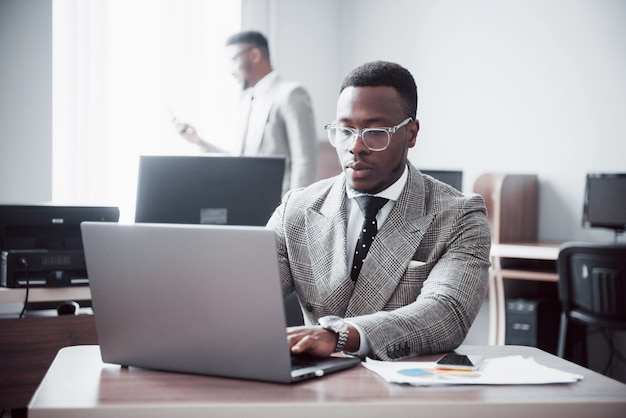Zwei hübsche fröhliche afroamerikaner-exekutivgeschäftsmann am arbeitsraumbüro