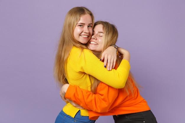 Zwei hübsche fröhliche junge blonde zwillingsschwestern mädchen in lebendigen bunten kleidern, die sich einzeln auf pastellvioletter blauer wand umarmen. menschen-familien-lifestyle-konzept.