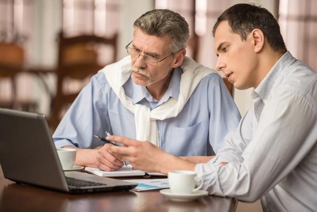 Zwei hübsche geschäftsmänner im städtischen café und in der anwendung des laptops.
