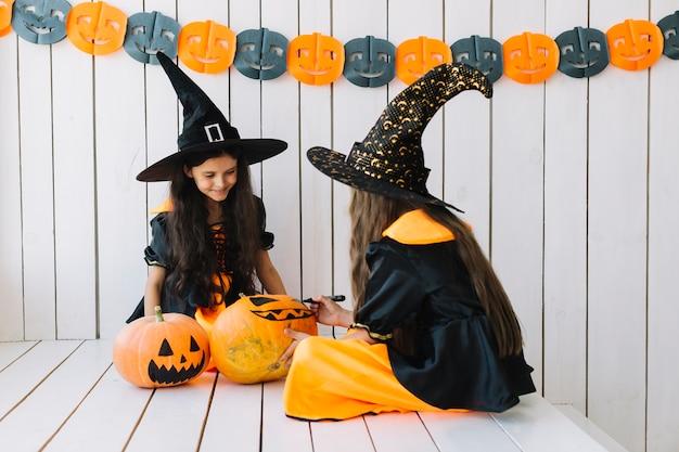 Zwei hübsche halloween-hexen, die kürbise malen