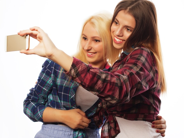 Zwei hübsche hipster-mädchen, die selfie machen. isoliert auf weißem hintergrund.