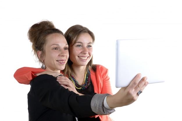 Zwei hübsche jugendlich mädchen, die selfies mit ihrem digitalen tablett nehmen