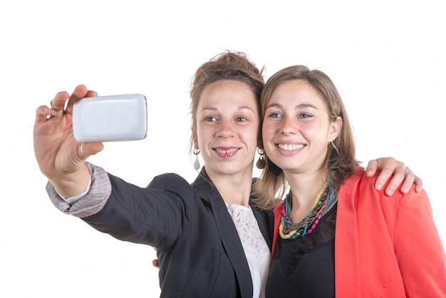 Zwei hübsche jugendlich mädchen, die selfies mit ihrem intelligenten telefon nehmen