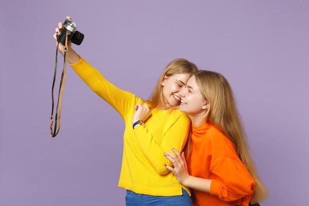 Zwei hübsche junge blonde zwillingsschwestern mädchen in bunten kleidern machen selfie-aufnahme auf retro-vintage-fotokamera isoliert auf violettblauer wand menschen-familien-lifestyle-konzept.