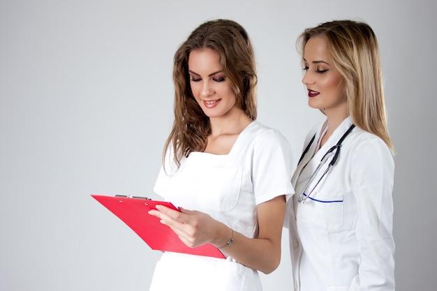 Zwei hübsche junge frauen ärzte, krankenschwestern suchen durch die patientin krankenschwester.