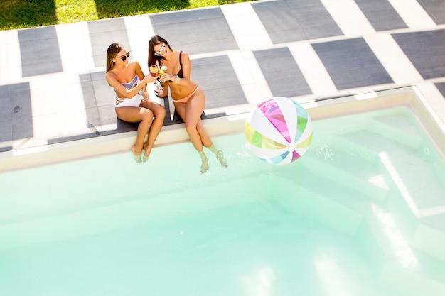 Zwei hübsche junge frauen am pool entspannen