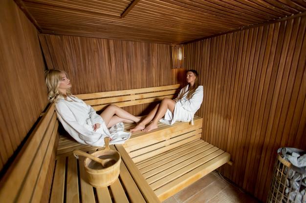 Zwei hübsche junge frauen, die sich in der sauna entspannen