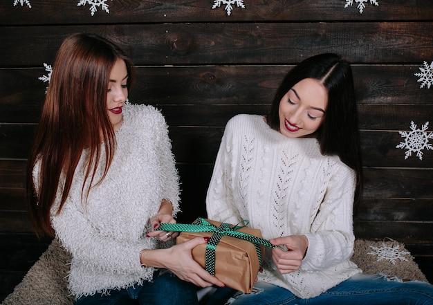 Zwei hübsche junge lustige freundinnen, die lächeln und spaß haben und feiertagsgeschenke halten