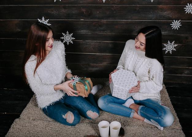 Zwei hübsche junge lustige freundinnen lächeln und geben sich gegenseitig geschenke