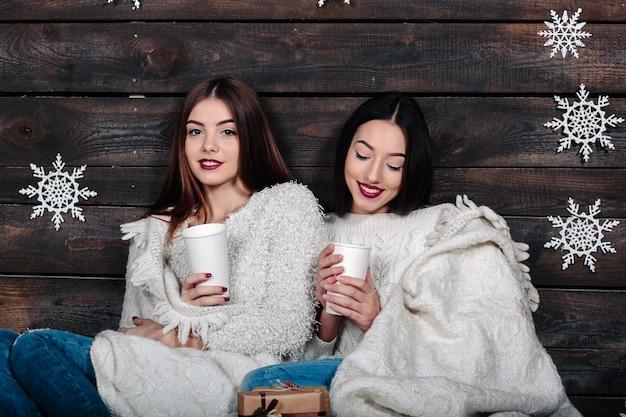 Zwei hübsche junge lustige freundinnen umarmen lächelnd und kuscheln zusammen