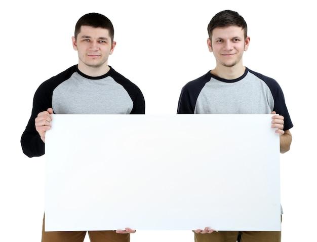 Zwei hübsche junge männer, die leeres plakat auf weiß halten