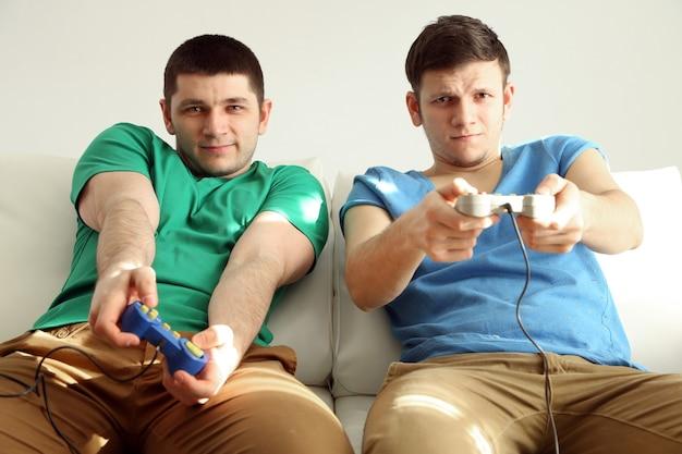 Zwei hübsche junge männer, die videospiele im raum spielen